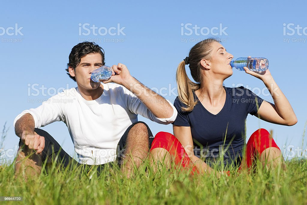 Young couple in activewear sitting down and drinking water royalty-free stock photo
