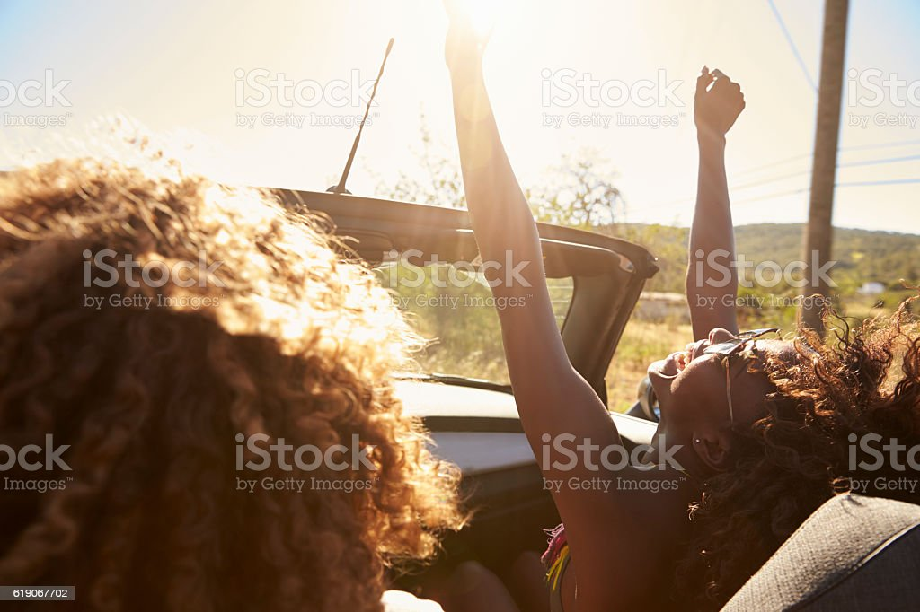 Young couple in an open top car, woman with arms raised stock photo