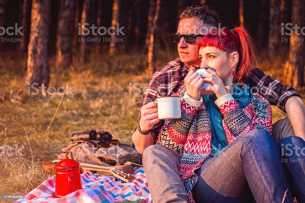 Young couple in autumn wood at picnic drinking tea stock photo