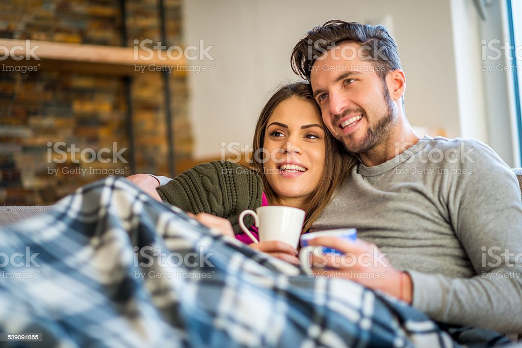 Young couple in bed with hot beverages stock photo