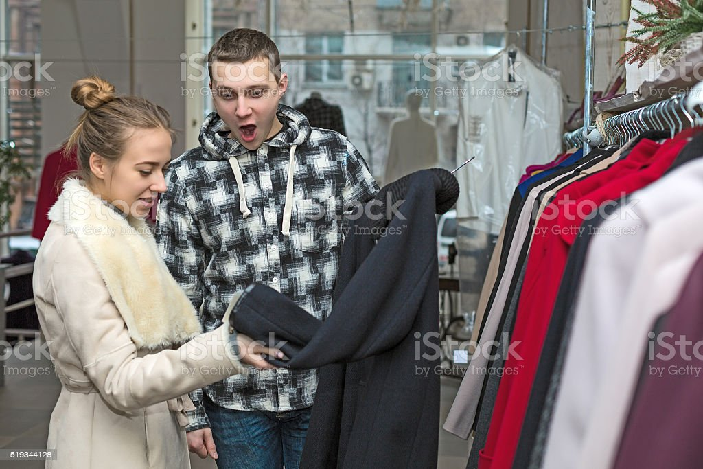 Young Couple in Clothing Shop Man excited stock photo