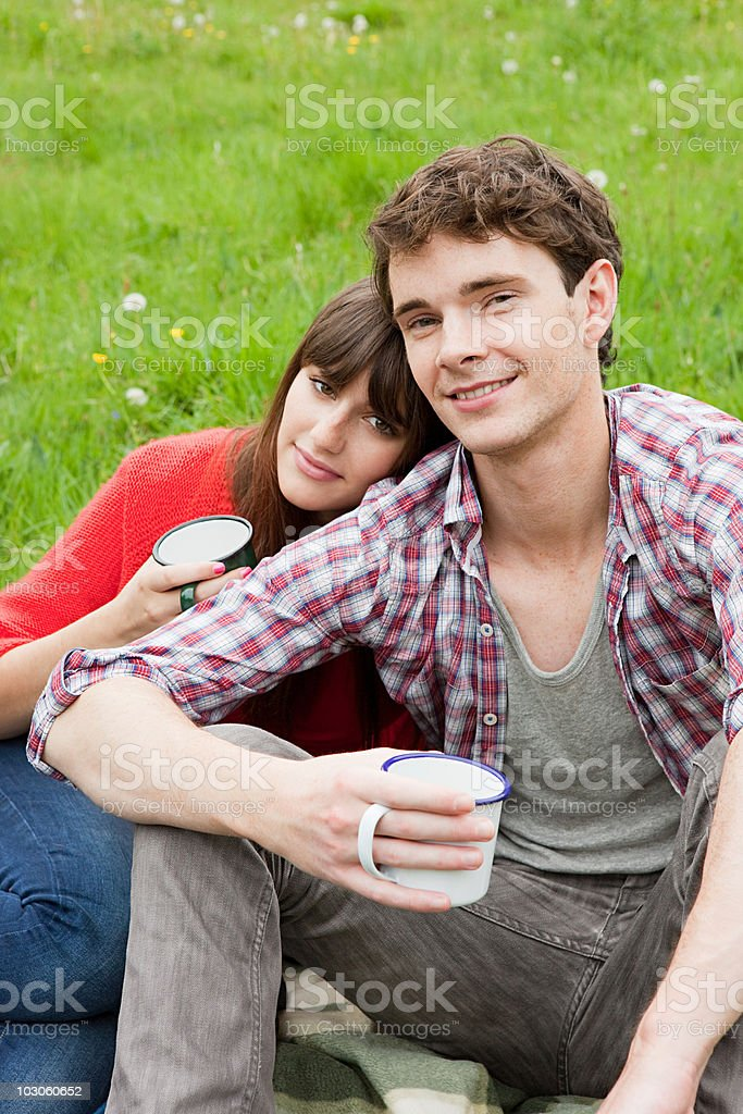Young couple in field with cups stock photo