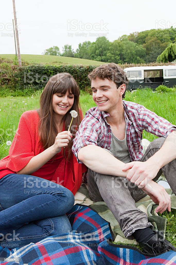 Young couple in field with dandelion clock royalty-free stock photo