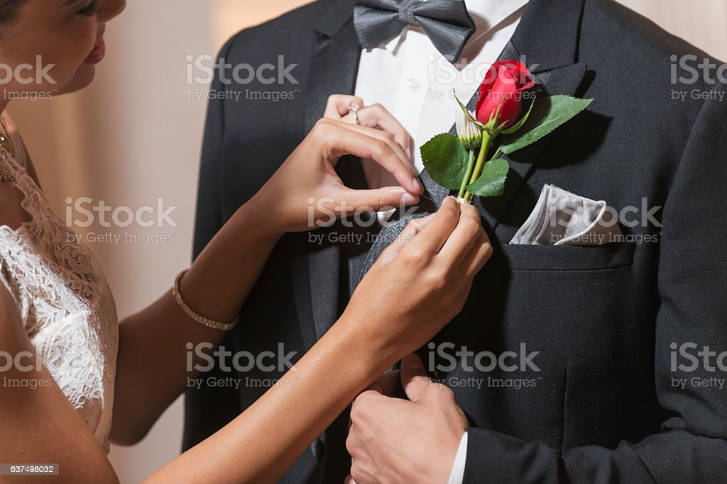 Young couple in formal attire, pinning boutonniere stock photo