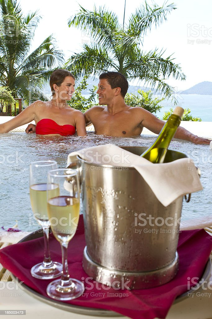 Young couple in jacuzzi with glasses of wine royalty-free stock photo