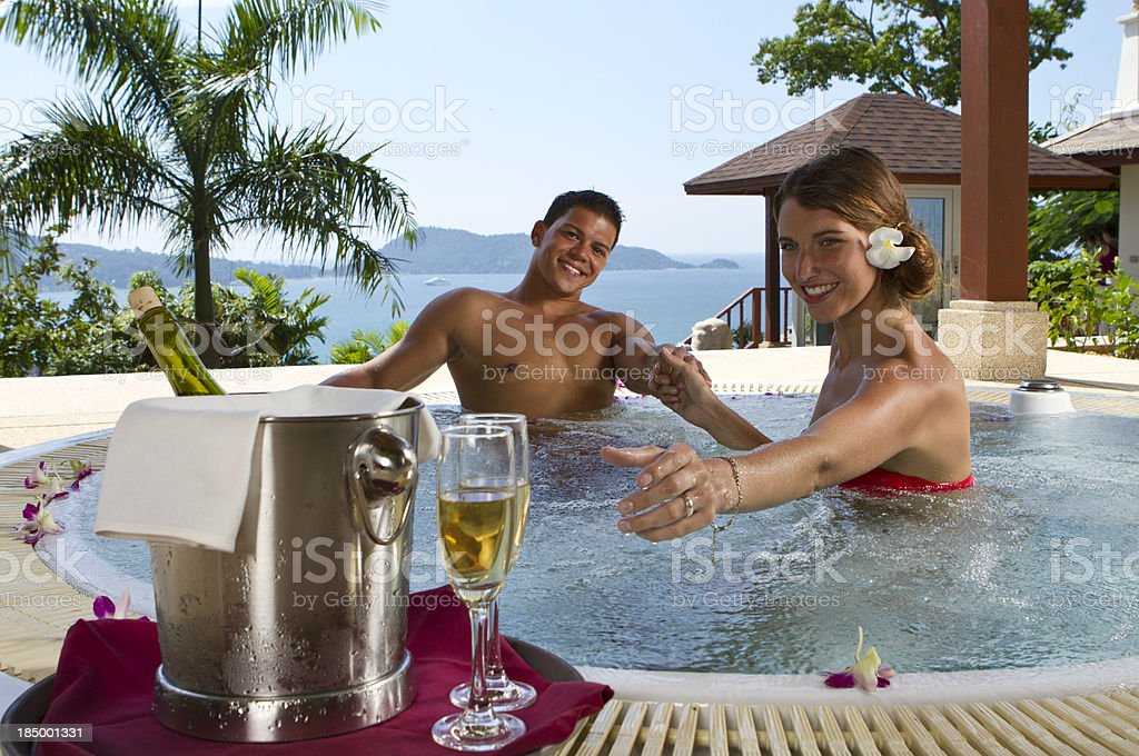 Young couple in jacuzzi with glasses of wine stock photo