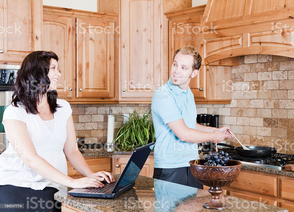 Young Couple in Kitchen Cooking and Using Computer royalty-free stock photo