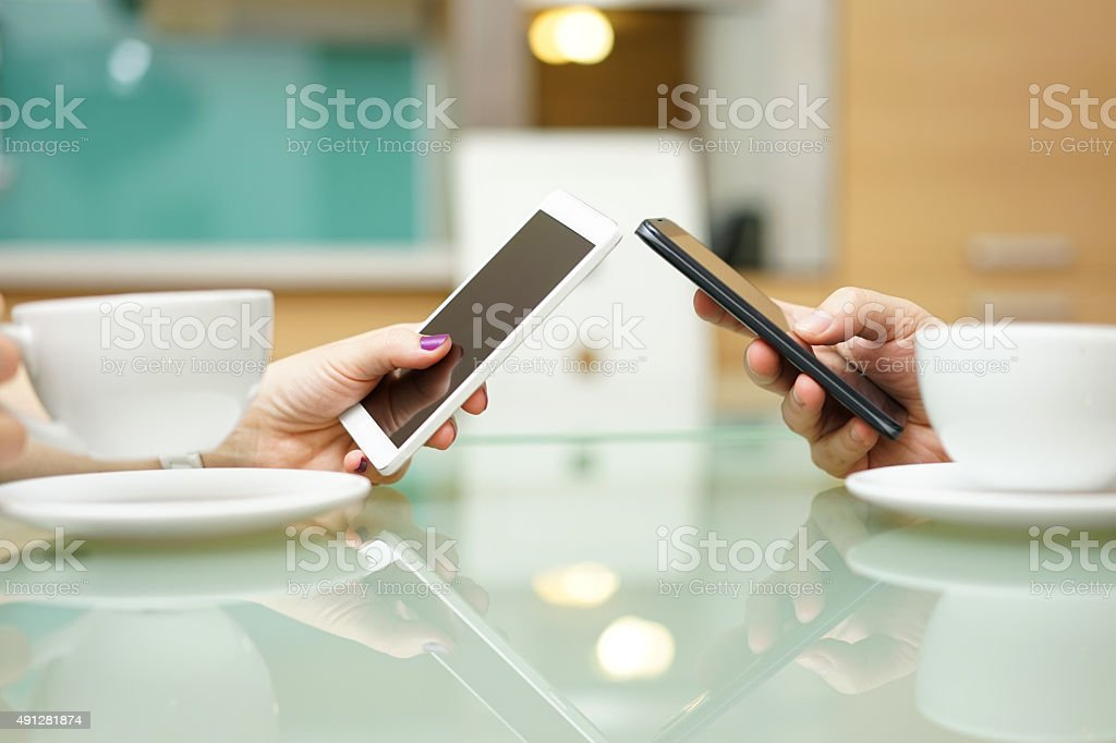 young couple in kitchen drinking coffee, using mobile phone stock photo