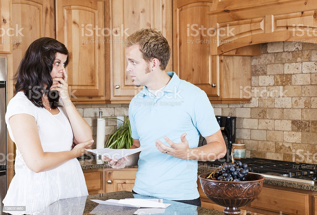 Young Couple in Kitchen Worrying about Bills royalty-free stock photo