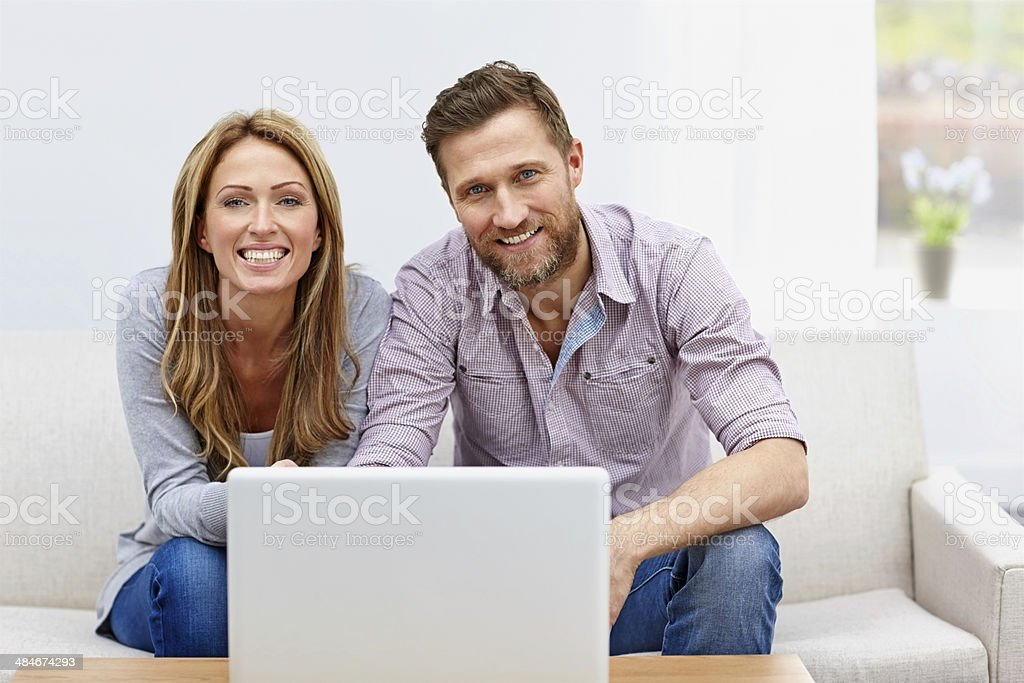 Young couple in living room with a laptop stock photo