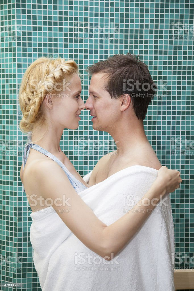 young couple in love embrace within towel by spa pool royalty-free stock photo