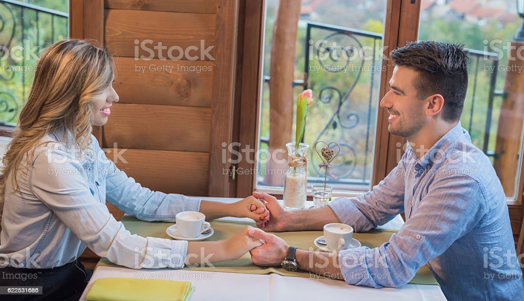 Young couple in love holding hands on a coffee break stock photo