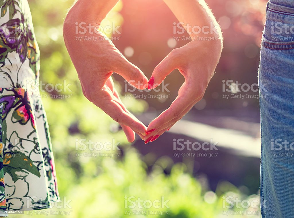 Young couple in love holding hands on the sunset during stock photo