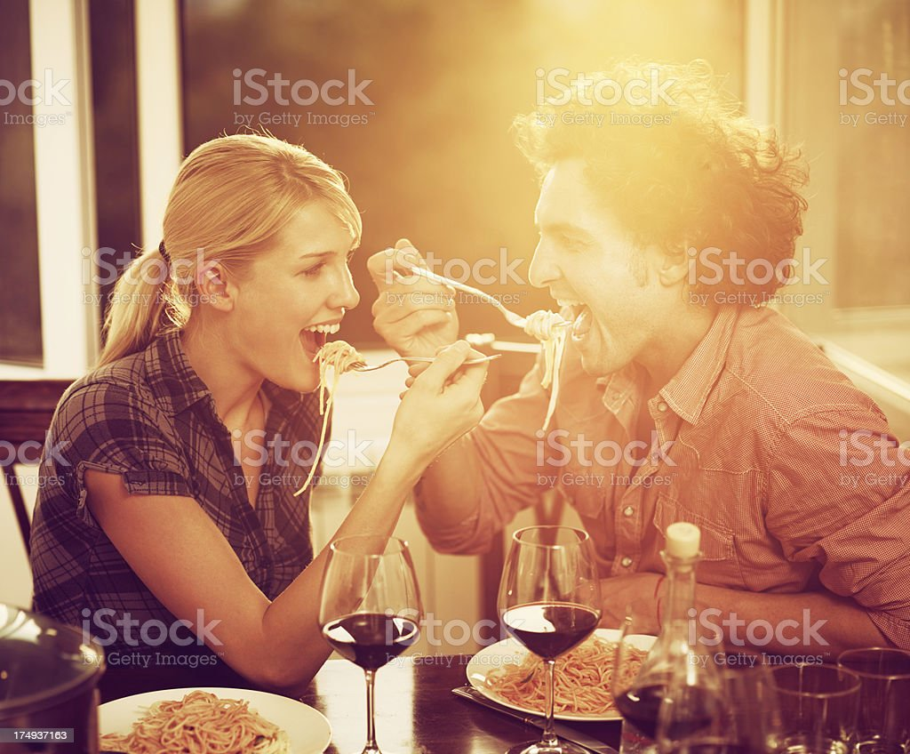 Young couple in love is enjoying wine and spagetti royalty-free stock photo