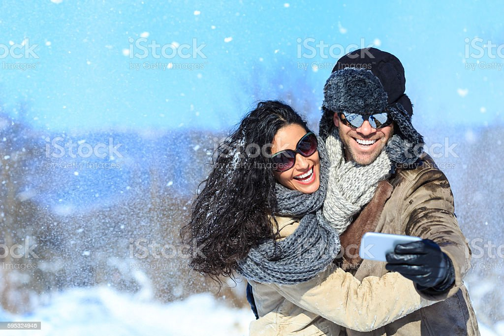 Smiling young couple having fun in the snow mountain, making selfie....