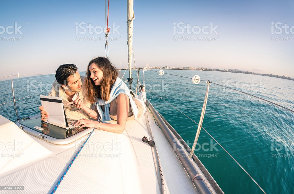 Young couple in love on sailboat having fun with tablet stock photo