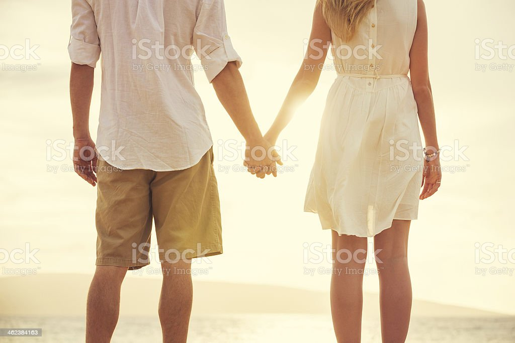 Young couple in love on the beach sunset stock photo