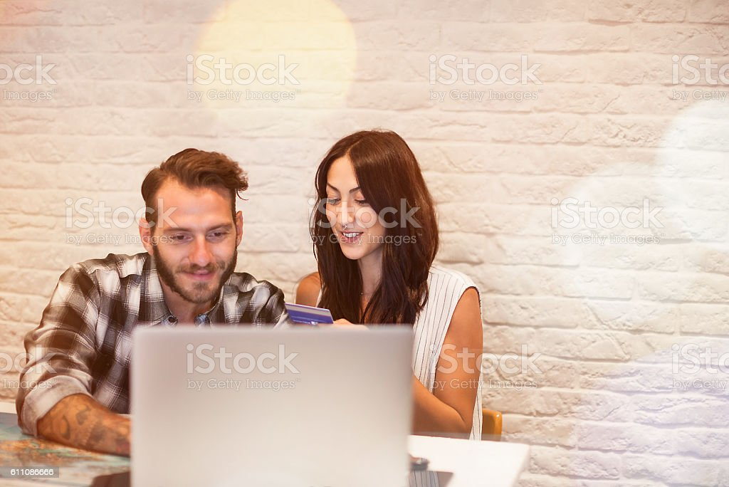Young couple in love planning a trip with laptop stock photo