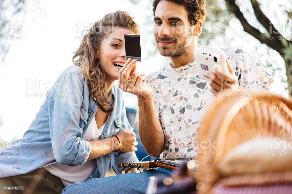 Young couple in love showing a printed selfie stock photo
