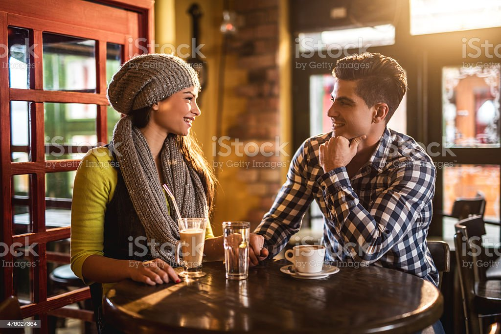 Young couple in love sitting in a cafe and communicating. stock photo