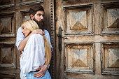 Young couple in love standing next to wooden door.