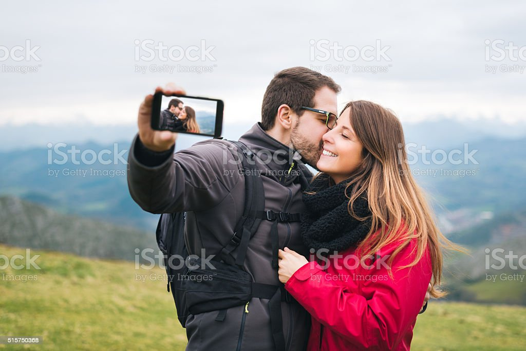 Young couple in love  taking selfie while kissing outdoor stock photo