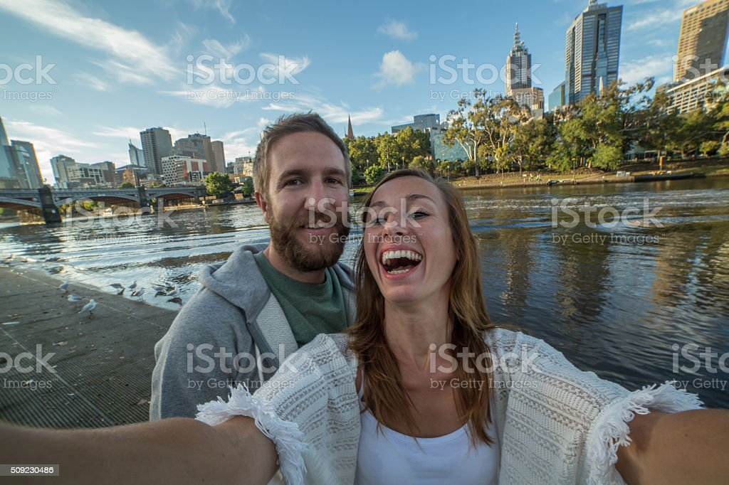 Young couple in Melbourne take selfie portrait along Yarra River stock photo