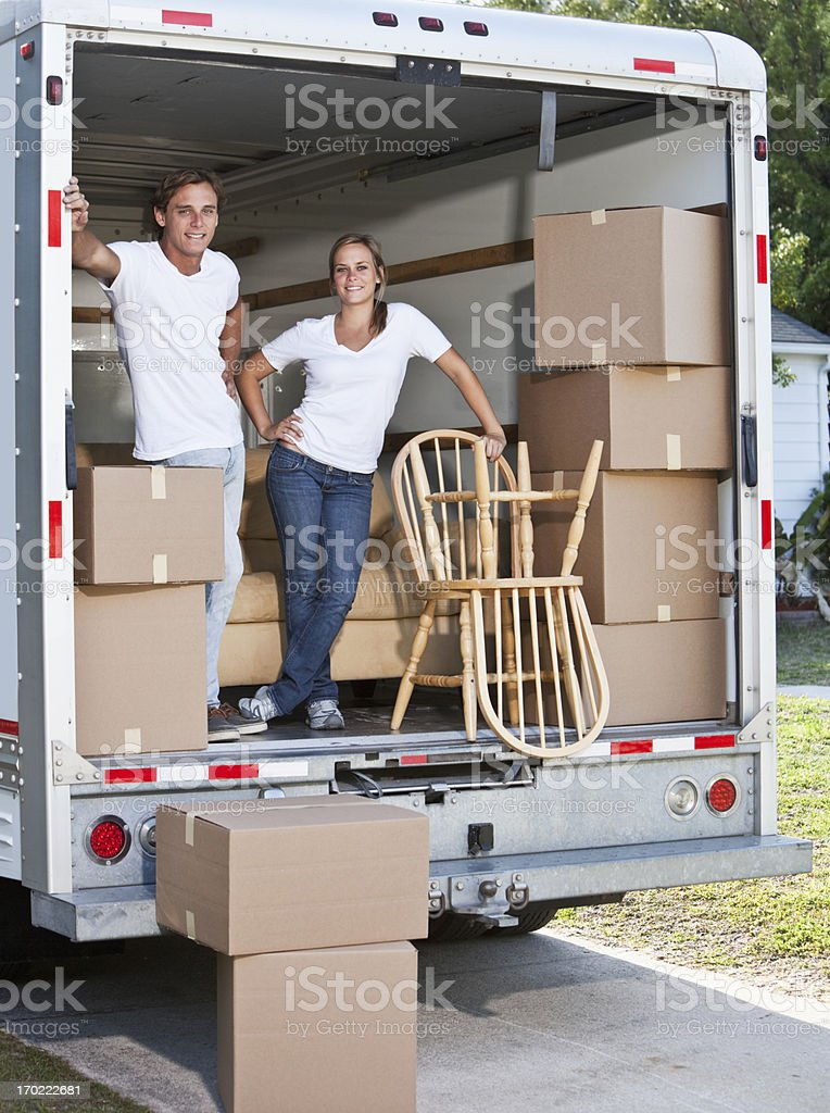 Young couple in moving van stock photo