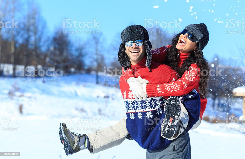 Young couple in piggyback ride on the snow mountain stock photo