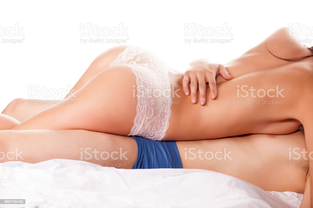 young couple in sensual embrace on white sheets stock photo