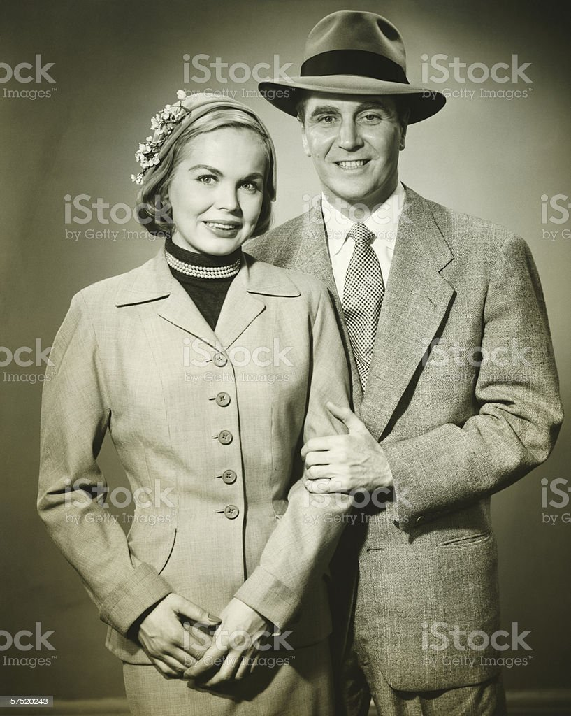Young couple in studio, man holding woman, smiling, (B&W), portrait royalty-free stock photo