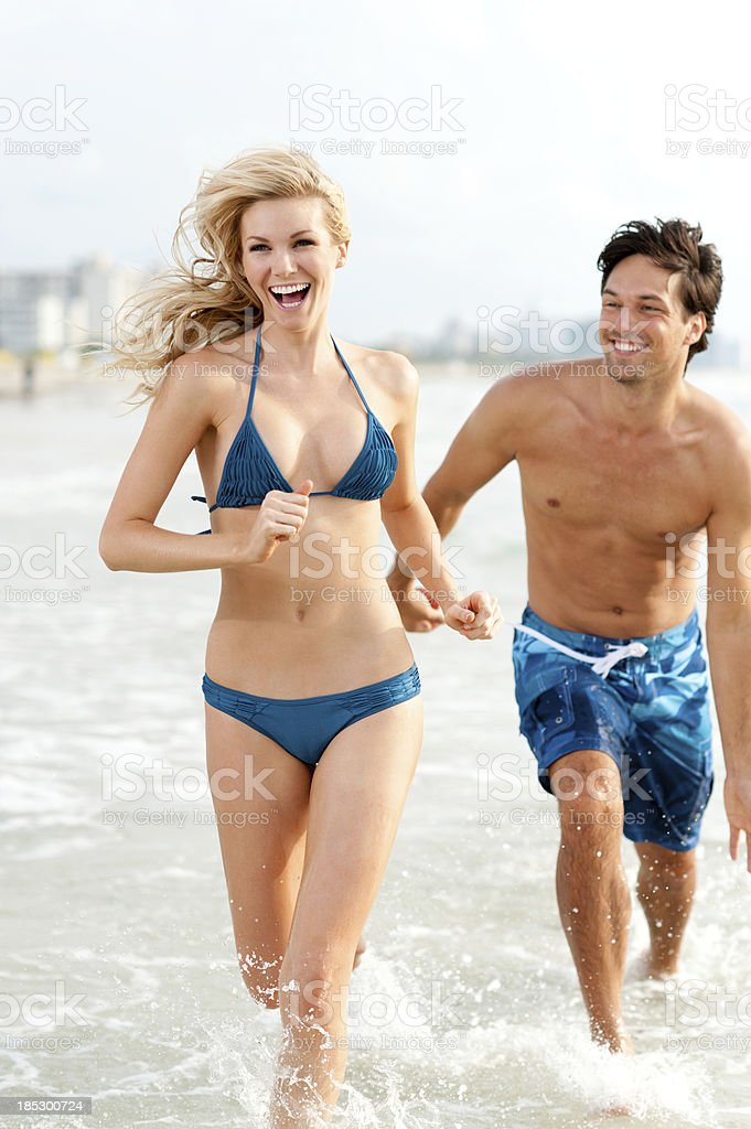 Young couple in swimwear running on beach royalty-free stock photo