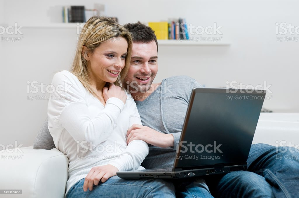 Young couple in the couch looking at laptop royalty-free stock photo
