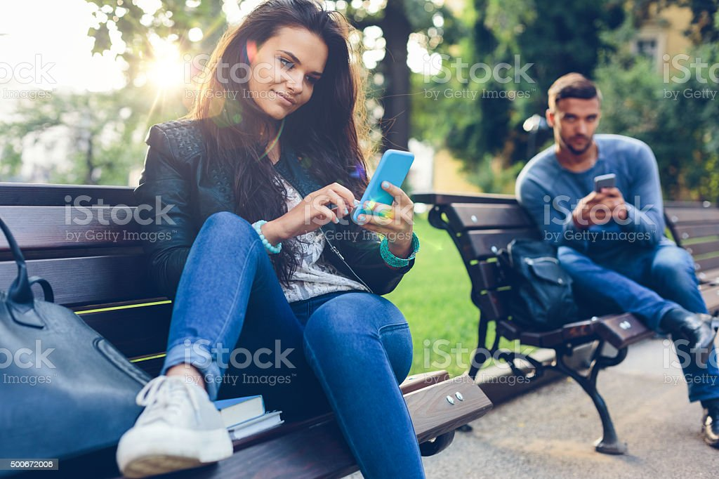 Young couple in the park texting on smartphones stock photo