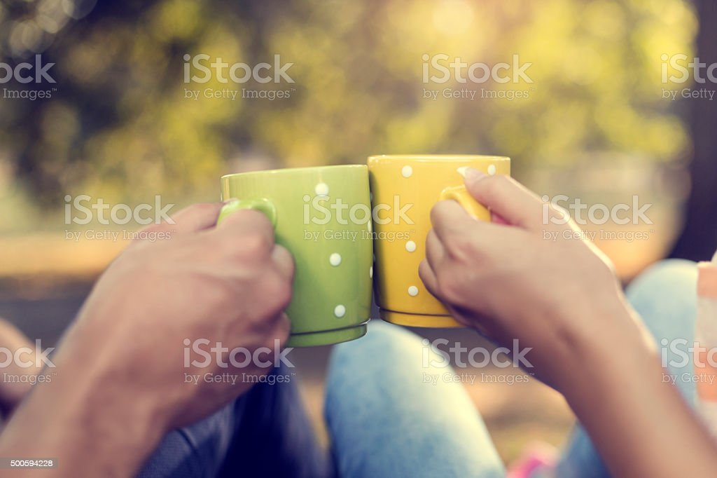Young couple in the park with coffee stock photo
