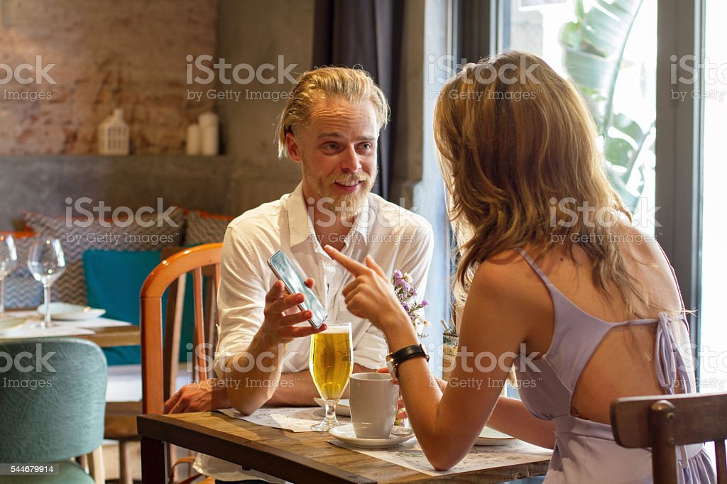 Young couple in the restaurant  with mobile phone stock photo