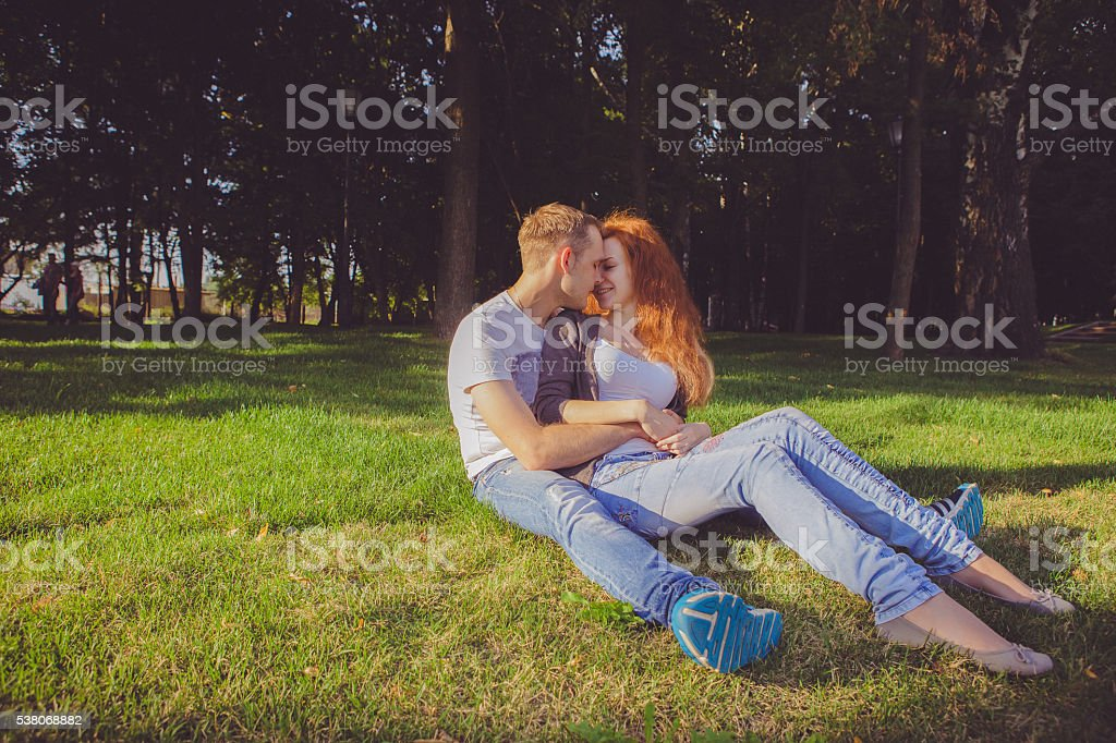 Young couple in the woods at sunset stock photo