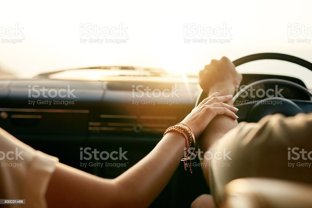 Young couple in their car holding hands stock photo