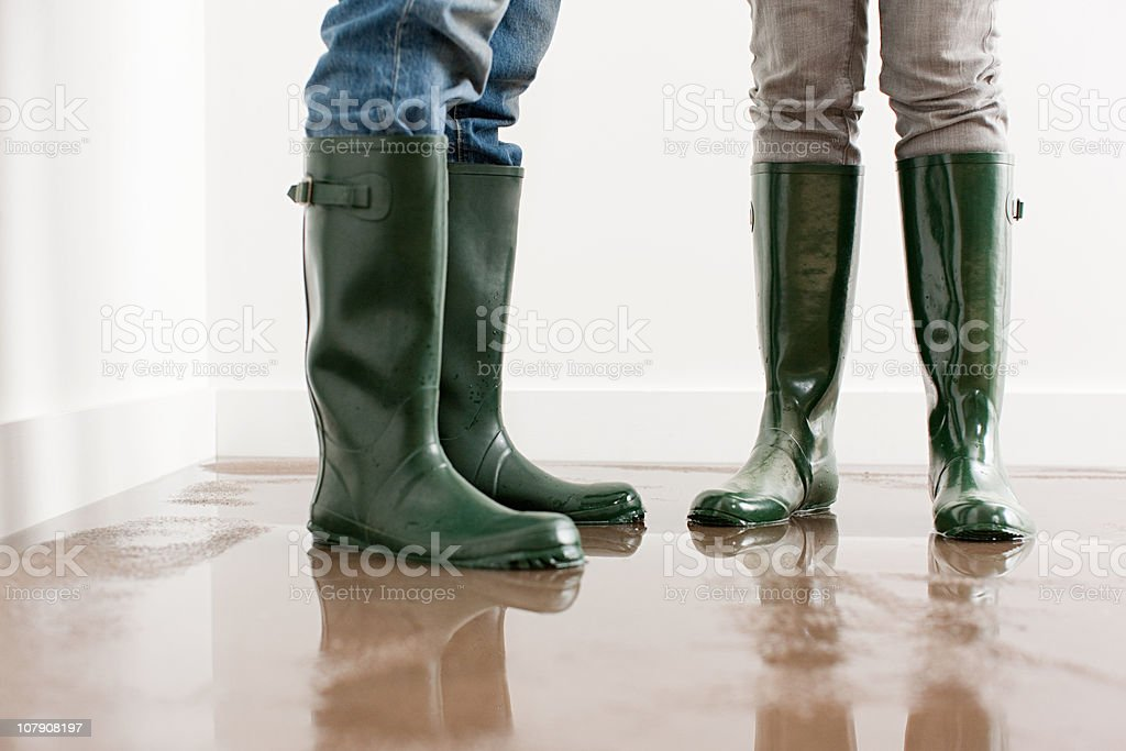 Young couple in wellington boots on flooded floor stock photo