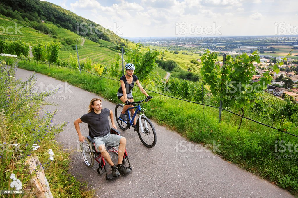 Young couple in wheelchair enjoying time outdoors stock photo