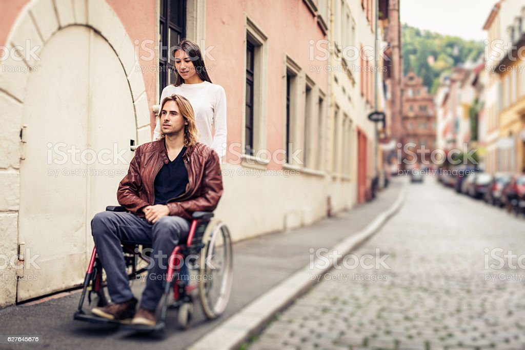 Young couple in wheelchair strolling in the city stock photo