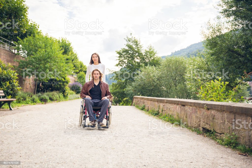 Young couple in wheelchair strolling in the park stock photo