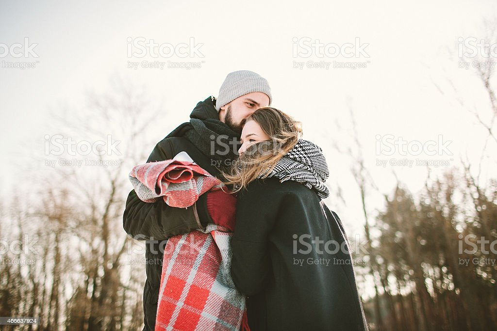 Young couple in winter forest with plaid and thermos stock photo