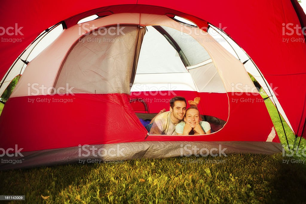 Young Couple Inside Big Red Tent Enjoying Outdoors and Camping royalty-free stock photo