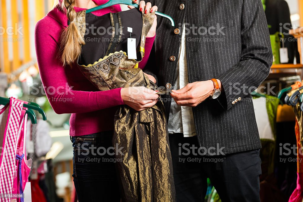 Young couple is buying Tracht or dirndl in a shop stock photo