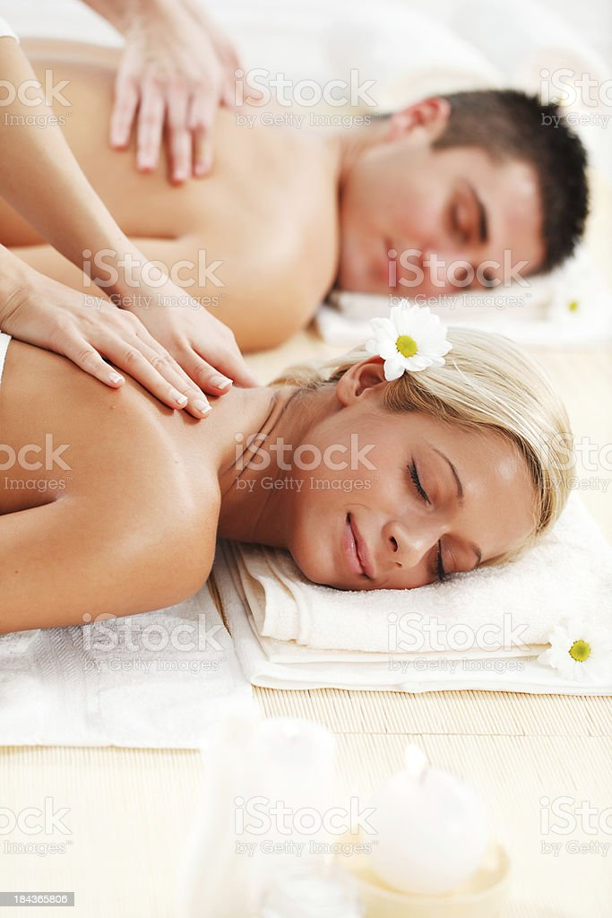Young couple is having a back massage at spa centre. royalty-free stock photo