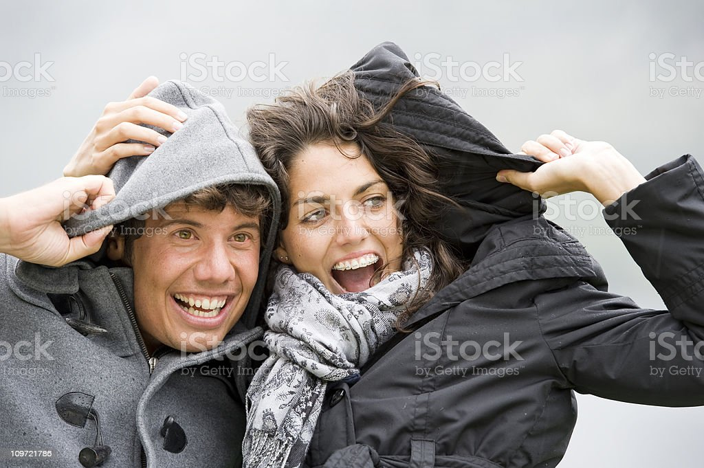 young couple is having fun on a rainy day stock photo
