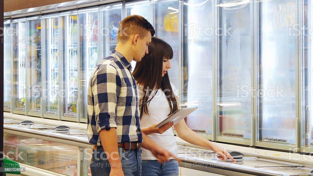 Young couple is standing by the freezer in grocery store foto de stock libre de derechos