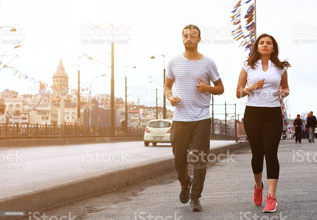 Young couple jogging in Istanbul, Galata Bridge... stock photo