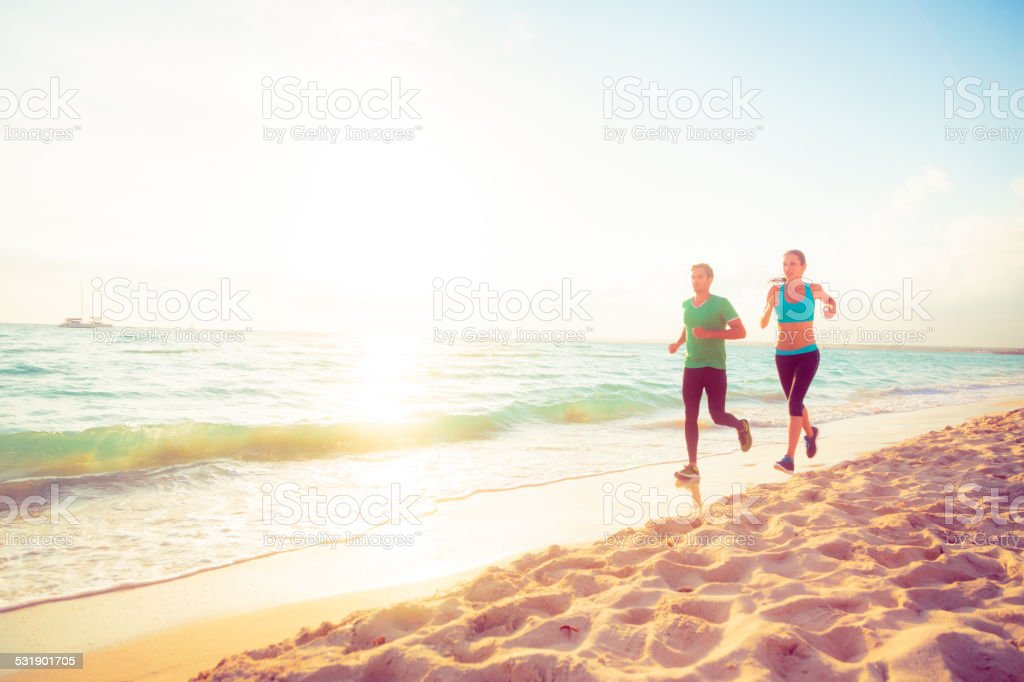 young couple jogging on the beach stock photo